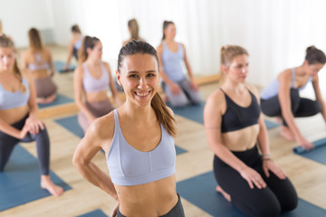 Fotomurales - Portrait of a cheerful beautiful young yoga instructor relaxing after giving yoga class to a large group of attractive sporty people. Healthy active lifestyle, working out indoors in gym.