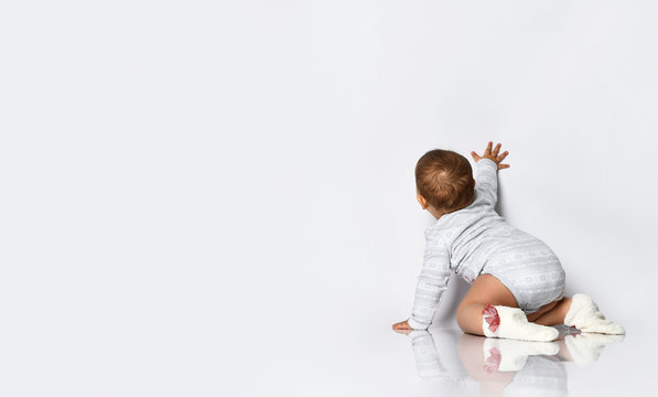 Baby girl in gray bodysuit and socks with red bows. She is creeping on the floor, touching wall, isolated on white. Back view
