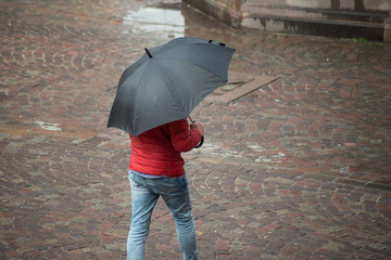 portrait of man walking with black umbrella and red coat on cobbles place