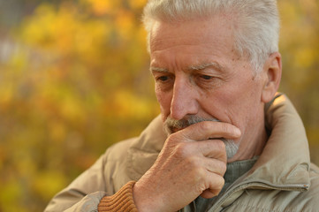 Portrait of thinking senior man in park