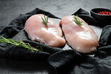 Foto op Plexiglas Kip Raw chicken fillet on a cutting Board. Fresh Breasts. Black background. Farm organic meat.