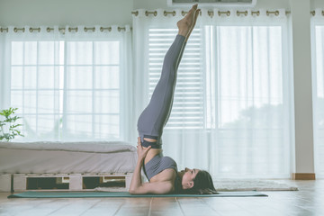In de dag Ontspanning Attractive Asian woman practice yoga Shoulder stand pose to meditation in bedroom after wake up in the morning Feeling so comfortable and relax,Healthcare Concept