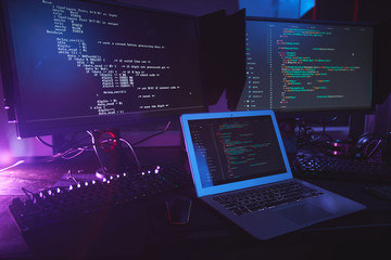 Background image of various computer equipment with programming code on screens on table in dark room, cyber security concept, copy space