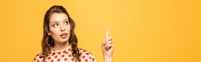 panoramic shot of thoughtful young woman looking up while showing idea gesture isolated on yellow
