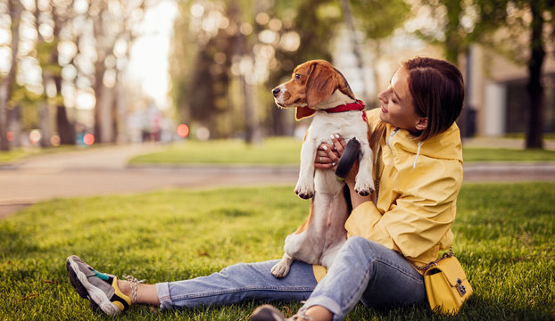 Cheerful woman with dog sitting in park