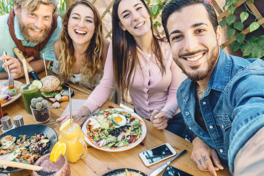 Happy friends taking selfie with mobile smartphone while lunching in coffee brunch restaurant - Young trendy people having fun eating together - Youth lifestyle food culture concept