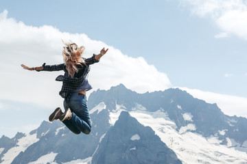 Woman hiker jumping on top of the mountain over blue skies