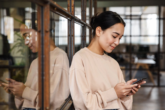 Image of young asian woman holding cellphone while working in office