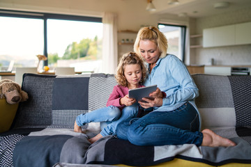 Wall Mural - A cute small girl with mother on sofa indoors at home, using tablet.