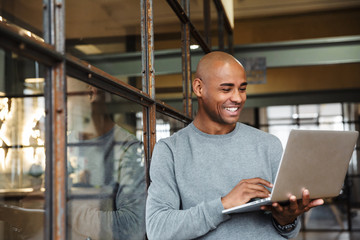 Image of bald african american man holding laptop while working in office