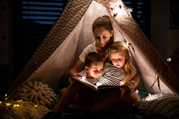 Mother with children sitting indoors in bedroom, reading a book. Fotobehang