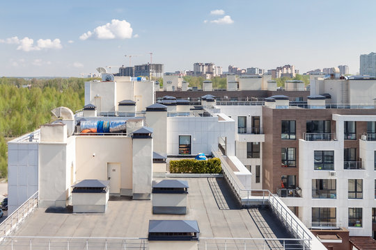 Flat roof with air conditioners on top modern apartment house building exterior mixed-use urban multi-family residential district area development.