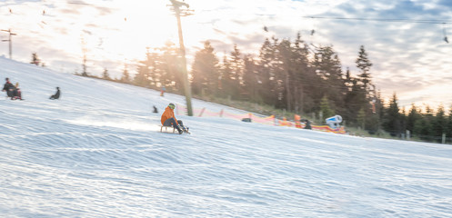 Young man sledding. Winter day in Winterberg. Sunshine. Motion blur and copy space.