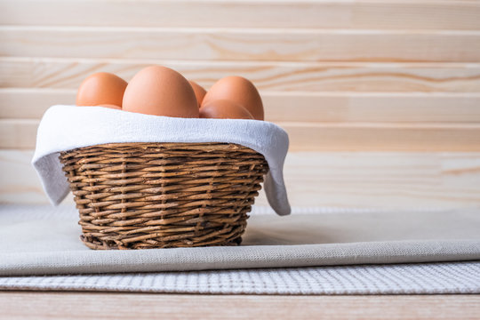 Brown fresh raw eggs on a white napkin in a small rough rustic basket.
