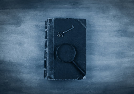 Old book, a key and a magnifying glass on the book against a worn wooden background with dark edges toned in the classic blue color (top view) as the crime story concept