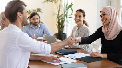 Smiling multiracial businesspeople handshake greeting at meeting