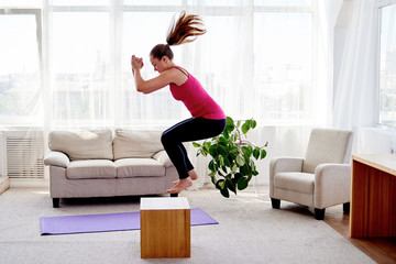 Young woman doing box jump exercise in living room at home, copy space. Jumping squats. Sport, healthy lifestyle concept
