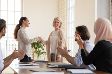 Smiling businesswoman handshake middle-aged employee greeting with employment