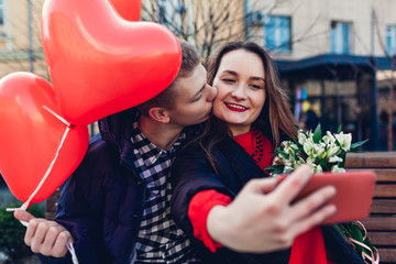 Valentines day. Couple in love taking selfie using smartphone with bouquet of flowers and balloons. Womens day