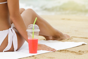 Woman with a red refreshing drink on the beach