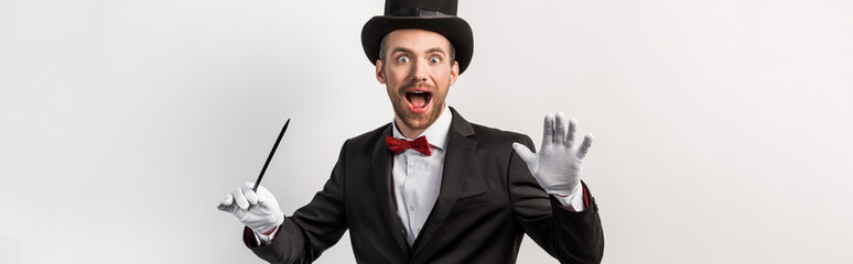 panoramic shot of excited magician in suit and hat holding wand, isolated on grey