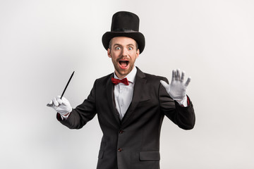 excited magician in suit and hat holding wand, isolated on grey