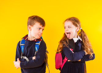 Funny kids in school uniform having fun together. Kids showing tongue each other