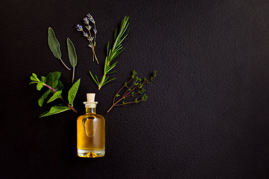 Essential oil of herbs for spa treatments. Bottle of natural oil with ingredients on black background, top view