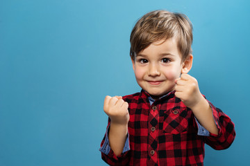 Portrait of small little caucasian boy young child kid standing in front of the blue wall background wearing red and black shirt looking to camera in studio holding fists in fighting stance position
