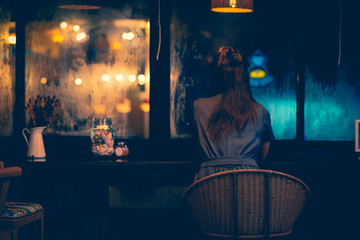 The only woman sitting in the coffee shop Lonely Facing outside on a rainy night with loneliness Picture tone dark style concept Loneliness on the night of love Valentine's Day