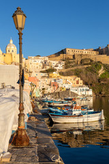 Procida (Italy) - View of Corricella bay in the sunset light, a romantic village of fishermen in Procida, Italy