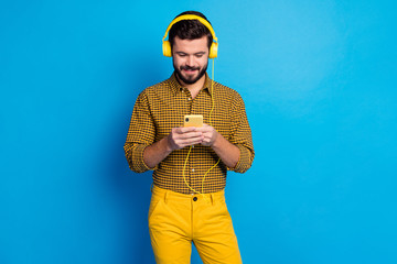 Portrait of positive cheerful man enjoy listen music stereo from his smartphone wear total yellow bright headset plaid trousers isolated over blue color background