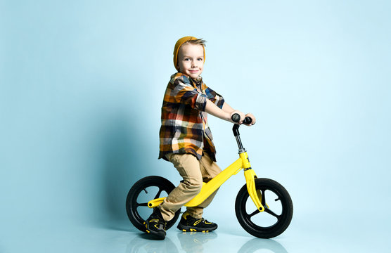 Boy in bright stylish casual clothing, sneakers, cap and round sunglasses standing near yellow run bike present