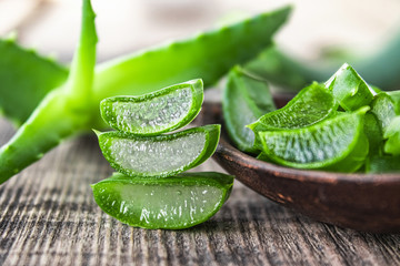 Fresh aloe vera leaves and slices of aloe vera in a spoon on a wooden background.