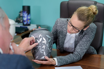 female funeral director showing urn to bereaved man