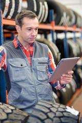 tire shop vendor reading information in tablet