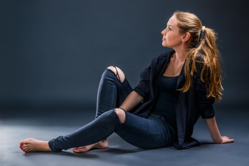 Young woman in ragged jeans resting sitting on the floor. Color photo