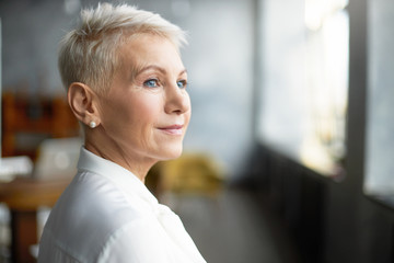 Close up profile shot of elegant short haired businesswoman wearing pearl earrings and stylish white blouse posing isolated in office interior, having pensive thoughtful look. Job, work and mature age Fotobehang