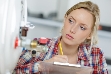 female plumber writing on clipboard