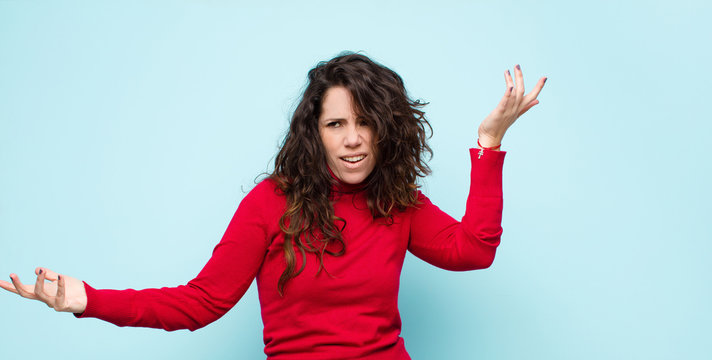 young pretty woman shrugging with a dumb, crazy, confused, puzzled expression, feeling annoyed and clueless against blue wall