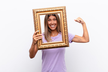 young pretty woman smiling with a happy, confident expression with hand on chin, wondering and looking to the side with a baroque frame.