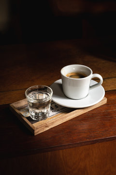 Cup with an espresso coffee in a wooden table