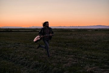 Bearded man with long hair in jeans and shirt running along wide field with guitar in hand