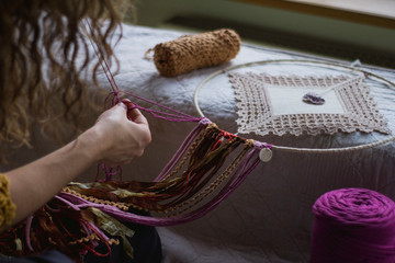 Back view of crop woman creating handmade dreamcatcher with long threads spending time in house