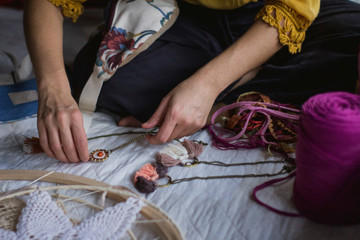 From above of crop female creating handmade dreamcatcher with long threads and accessories sitting in house