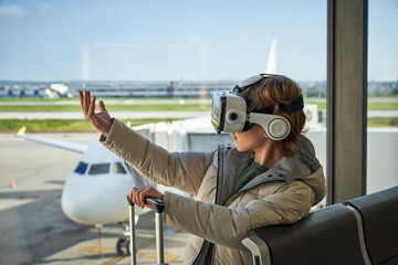 Preteen boy in hooded outwear and VR goggles gesturing and exploring virtual reality while sitting near window in modern airport