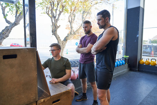 Personal trainer in gym giving directions to two boys to do multifunctional training