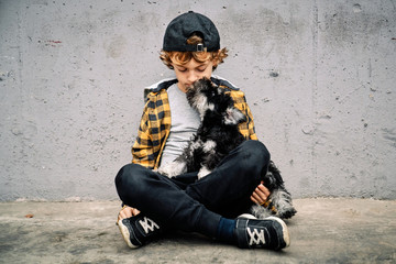 Unhappy sad boy in checkered shirt and cap sitting with eyes closed next to concrete wall on street and holding Yorkshire Terrier puppy