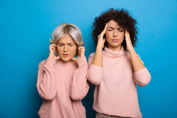 Attractive young curly woman with her female best friend touching their head with both because having headache isolated on blue wall.