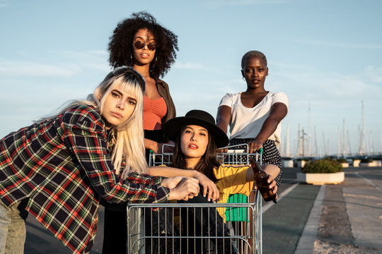 Multiracial group of young women standing around shopping cart on road